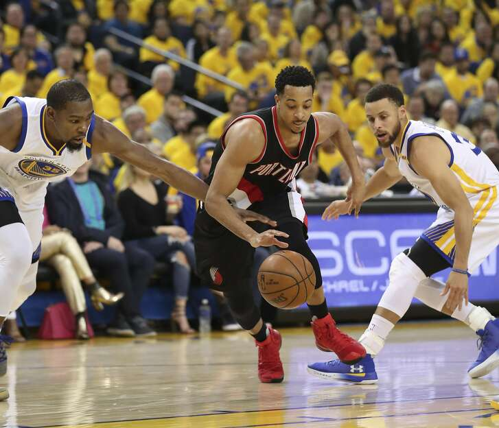 Portland Trailblazers' CJ McCollum gets past Golden State Warriors' Kevin Durant and Stephen Curry in the second quarter during Game 1 of the First Round of the Western Conference 2017 NBA Playoffs at Oracle Arena on Sunday, April 16, 2017 in Oakland, Calif.