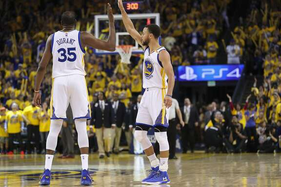 Golden State Warriors' Kevin Durant and Stephen Curry high five in the third quarter during Game 1 of the First Round of the Western Conference 2017 NBA Playoffs at Oracle Arena on Sunday, April 16, 2017 in Oakland, Calif.
