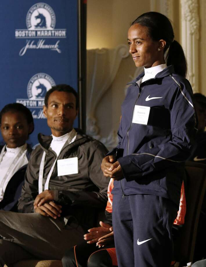 Top-seeded distance runners Atsede Baysa, left, and Lemi Berhanu Hayle, center, watch Buzunesh Deba, all of Ethiopia, stand during a Boston Marathon media availability Friday, April 14, 2017, in advance of Monday's race in Boston. In 2016, Deba was named the 2014 Boston Marathon winner following the disqualification of Rita Jeptoo, of Kenya, for doping. (AP Photo/Bill Sikes) Photo: Bill Sikes/Associated Press