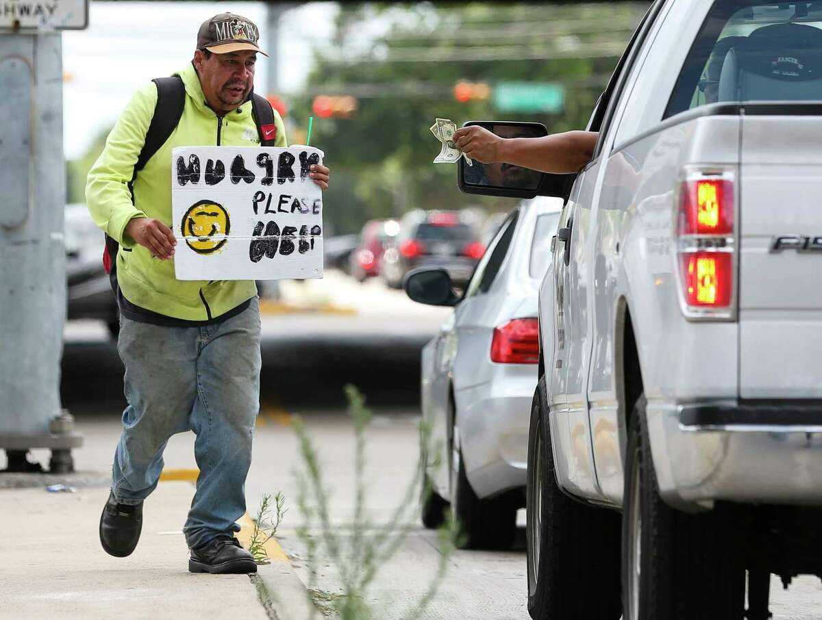 A driver hands a few dollars to Andrew Quintanilla at a Southwest Freeway feeder road intersection Friday. Because of a new ordinance prohibiting blocking medians and other spaces, seeking donations this way could be subject to a Class C misdemeanor.