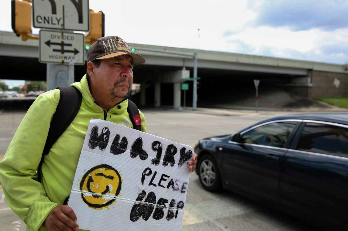 Andrew Quintanilla stands on the median and panhandles at the intersection of Southwest Freeway and Weslayan Street Friday in Houston.