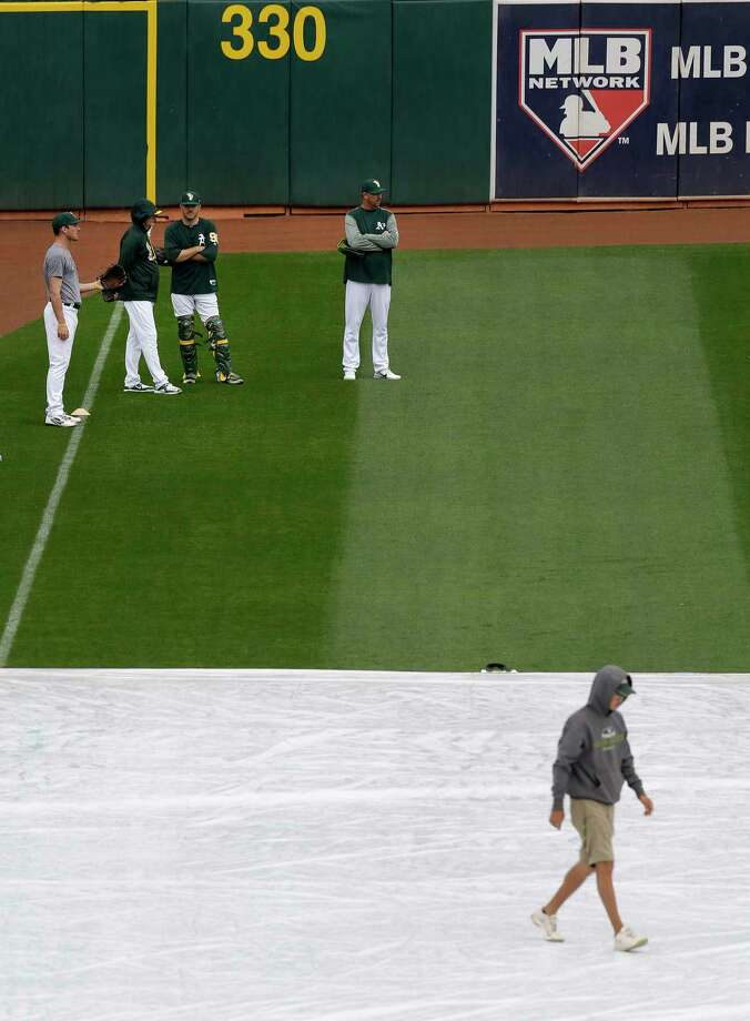 Oakland Athletics prepare for the baseball game against the Houston Astros as a groundskeeper walks on a tarp covering the infield on Sunday in Oakland, Calif. Photo: Ben Margot, STF / Copyright 2017 The Associated Press. All rights reserved.