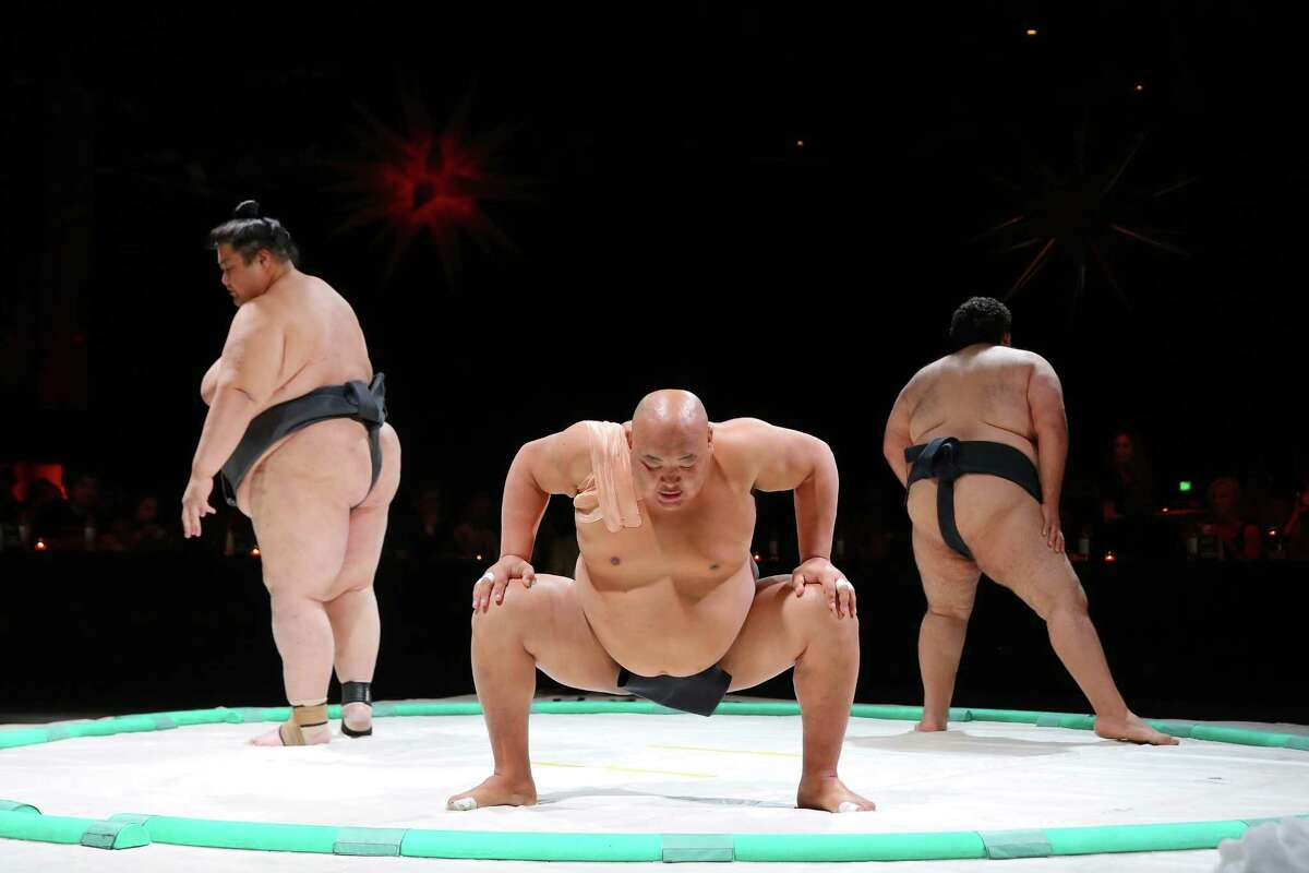 Ryuichi Yamamoto, left, Byambajav Ulambayar, center, and Ramy Elgazar, warm up before sparing with each other during the 2nd annual Sushi + Sumo event put on by SE Productions at the WaMu Theater, Saturday, April 15, 2017. Guests enjoyed a sushi dinner while watching sumo wrestling bouts between three internationally recognized wrestlers.