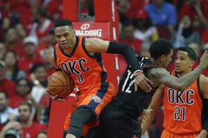 Thunder guard Russell Westbrook (0) pushes aside Rockets guard Lou Williams (12) for a rebound during the second half Sunday night.