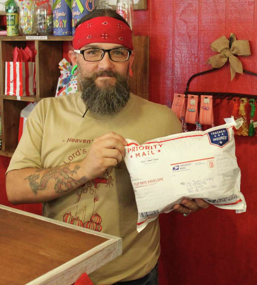 Jason Bleau, co-owner of Sissy's Sweet Shack, holds a large package filled with donated candy to be sent to an Army Post Office for the Treats for Troops program. Photo: Jacob McAdams
