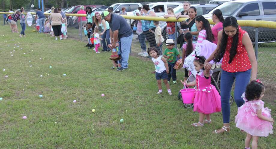 Parents struggle to restrain their kids at the Shepherd Youth League baseball field where the McClain's Easter Egg hunt is hosted every year. This year's event was held on April 15. Photo: Jacob McAdams
