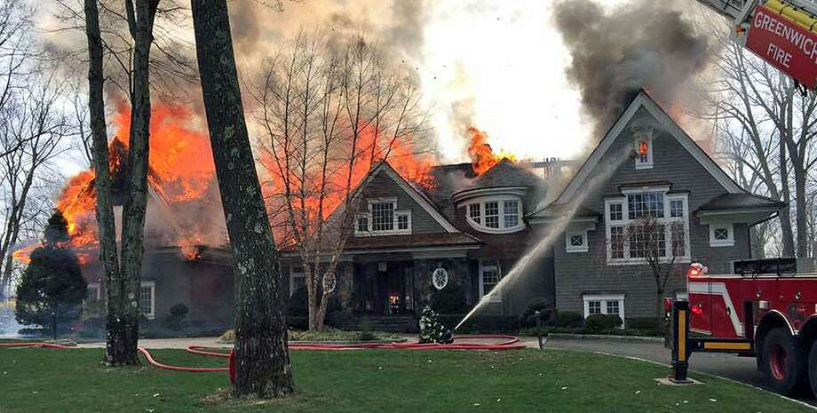 Firefighters attempt to quell a blaze on Londonderry Drive in Greenwich Sat., April 15, 2017. The cause of the fire was under investigation Monday. Officials said the distance from the closest fire hydrant, some 2000 feet, complicated the response. Photo: Contributed Photo / Greenwich Professional Firefighters / Contributed Photo / Connecticut Post