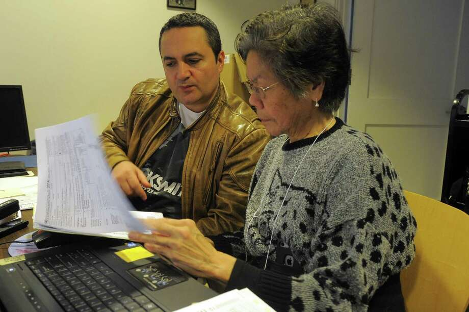 Norwalk resident and AARP volunteer Iris Kishimoto of Norwalk assists Claudio Tudora of Stamford with his 2015 tax return, in April 2016. Photo: Matthew Brown / Hearst Connecticut Media / Stamford Advocate
