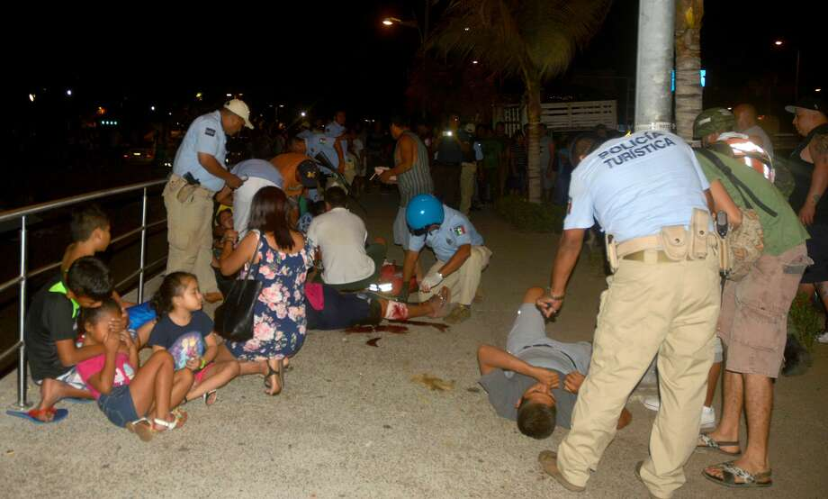 Members of Acapulco tourist police attend injured tourists after a shootout on April 15, 2017 in Acapulco, Mexico. A shootout in the tourist area of the resort left one dead and seven wounded on Saturday night, local authorities reported. / AFP PHOTO / FRANCISCO ROBLES        (Photo credit should read FRANCISCO ROBLES/AFP/Getty Images) Photo: AFP/AFP/Getty Images