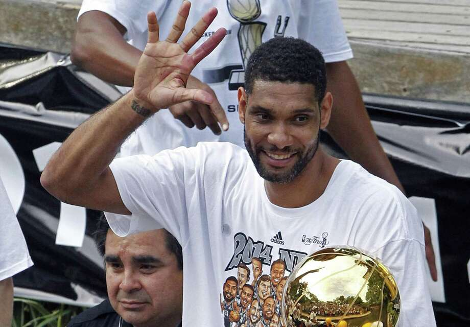 Tim Duncan shows fans how many league titles the Spurs have won during the 2014 river parade. Photo: Michael Thomas /Associated Press / FR65778 AP