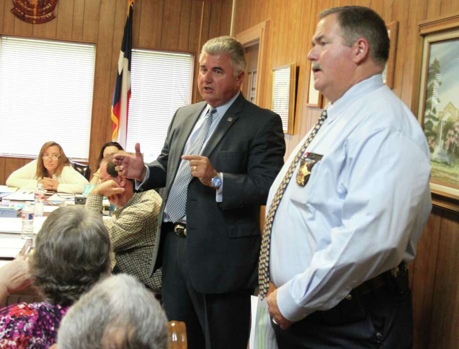 TECSIQ President Allen Fletcher (left) explains the benefits of the company's warranty technology for law enforcement agencies during the San Jacinto County Commissioners Court on April 11. Photo: Jacob McAdams
