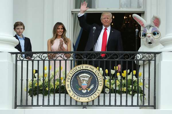 President Donald Trump (C) waves to guests after delivering remarks from the Truman Balcony with first lady Melania Trump and their son Barron Trump (L) during the 139th Easter Egg Roll on the South Lawn of the White House April 17, 2017 in Washington, DC. The White House said 21,000 people are expected to attend the annual tradition of rolling colored eggs down the White House lawn that was started by President Rutherford B. Hayes in 1878.