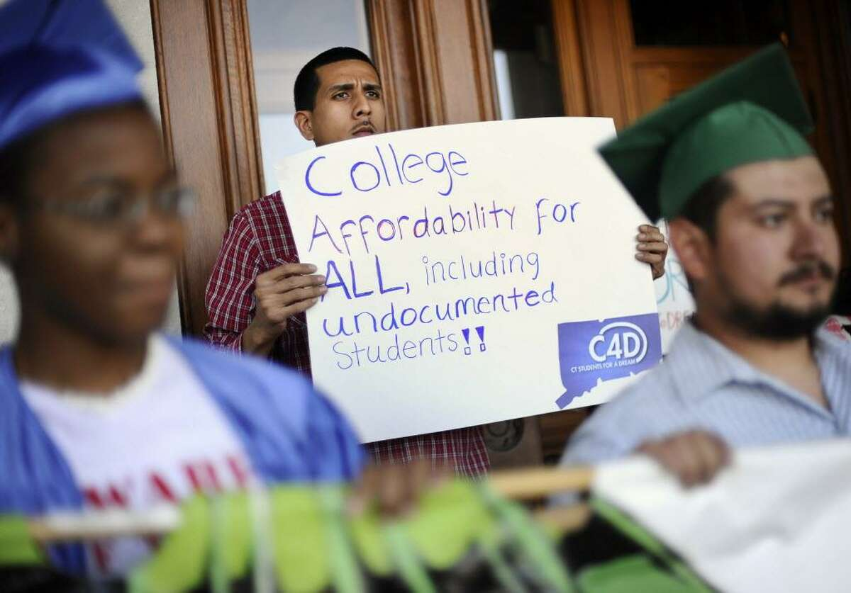 Francisco Dominguez of Hartford, Conn., holds a sign in support for financial aid for non-citizen college students during a rally at the state Capitol, Tuesday, May 20, 2014, in Hartford. Students brought to the U.S. illegally as children are asking Connecticut Gov. Dannel P .Malloy to help them obtain institutional financial aid. Six students met privately with the Democrat in his office on Tuesday. They're part of a group called Connecticut Students for a DREAM, which persuaded Malloy to meet with them after appearing at several of his recent town hall events. (AP Photo/Jessica Hill)