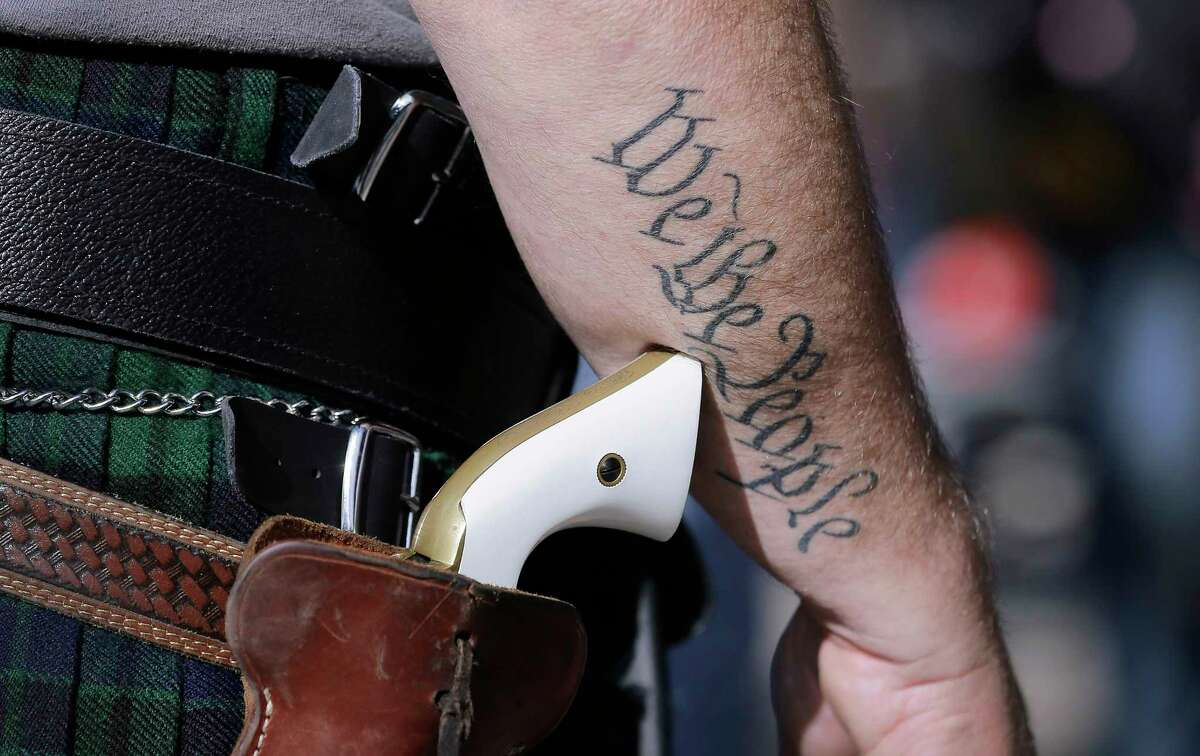 An open-carry gun laws supporter displays his holstered pistol at a rally in front of the state Capitol.