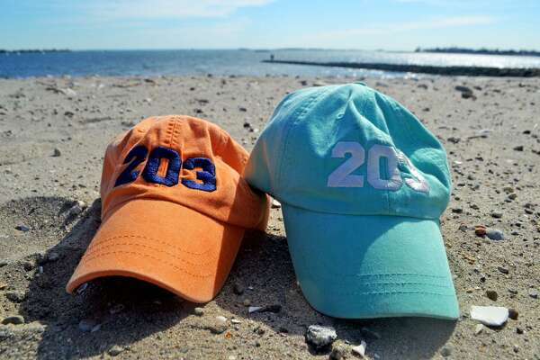 Two Oh Three's embroidered baseball caps sit on the sand at Compo Beach in Westport.