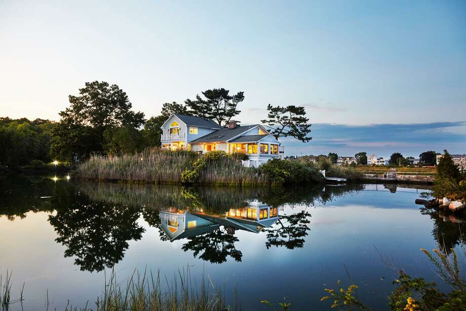 The contemporary split level house at 5 Langdon Road on Canfield Island is a private waterfront oasis with a lagoon, beach, dock and outdoor fireplace.