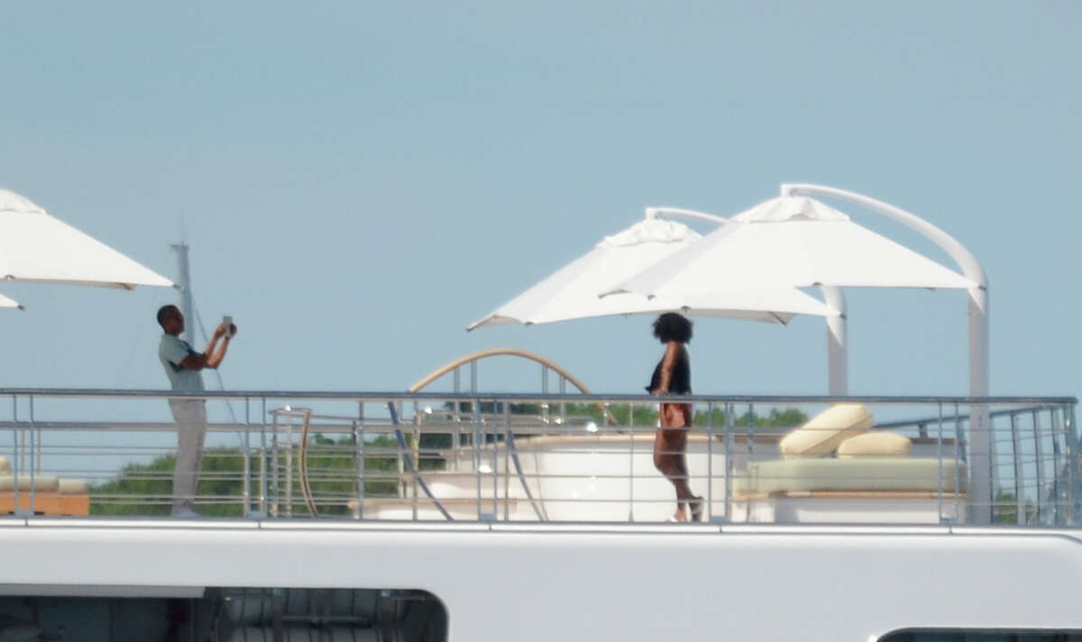 Former US President Obama takes a holiday snap of his wife Michelle, as she poses on the top deck of the 138 meter Rising Sun yacht where the couple and friends spent the morning off the Island of Moorea, in the South Pacific, part of French Polynesia on April 14, 2017. Obama and his wife Michelle, US singer Bruce Springsteen, US actor Tom Hanks and TV personality Oprah Winfrey, spent two hours aboard the Rising Sun before leaving Tahiti. The Obamas left Tahiti after a one-month stay in French Polynesia.