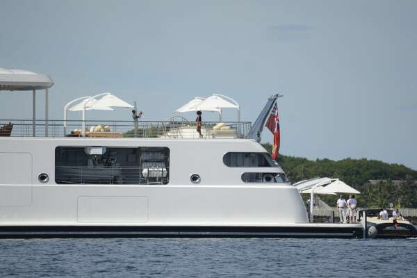 CORRECTION - Former US President Obama take a holiday snap of his wife Michelle, as she poses on the top deck of the 138 meter Rising Sun yacht where the couple and friends spent the morning off the Island of Moorea, in the South Pacific, part of French Polynesia on April 14, 2017.  Obama and his wife Michelle, US singer Bruce Springsteen, US actor Tom Hanks and TV personality Oprah Winfrey, spent two hours aboard the Rising Sun before leaving Tahiti. The Obamas left Tahiti after a one-month stay in French Polynesia.  / AFP PHOTO / Mike LEYRAL / The erroneous mention[s] appearing in the metadata of this photo by Mike LEYRAL has been modified in AFP systems in the following manner: [April 14, 2014] instead of [April 24 2017]. Please immediately remove the erroneous mention[s] from all your online services and delete it (them) from your servers. If you have been authorized by AFP to distribute it (them) to third parties, please ensure that the same actions are carried out by them. Failure to promptly comply with these instructions will entail liability on your part for any continued or post notification usage. Therefore we thank you very much for all your attention and prompt action. We are sorry for the inconvenience this notification may cause and remain at your disposal for any further information you may require.        (Photo credit should read MIKE LEYRAL/AFP/Getty Images)