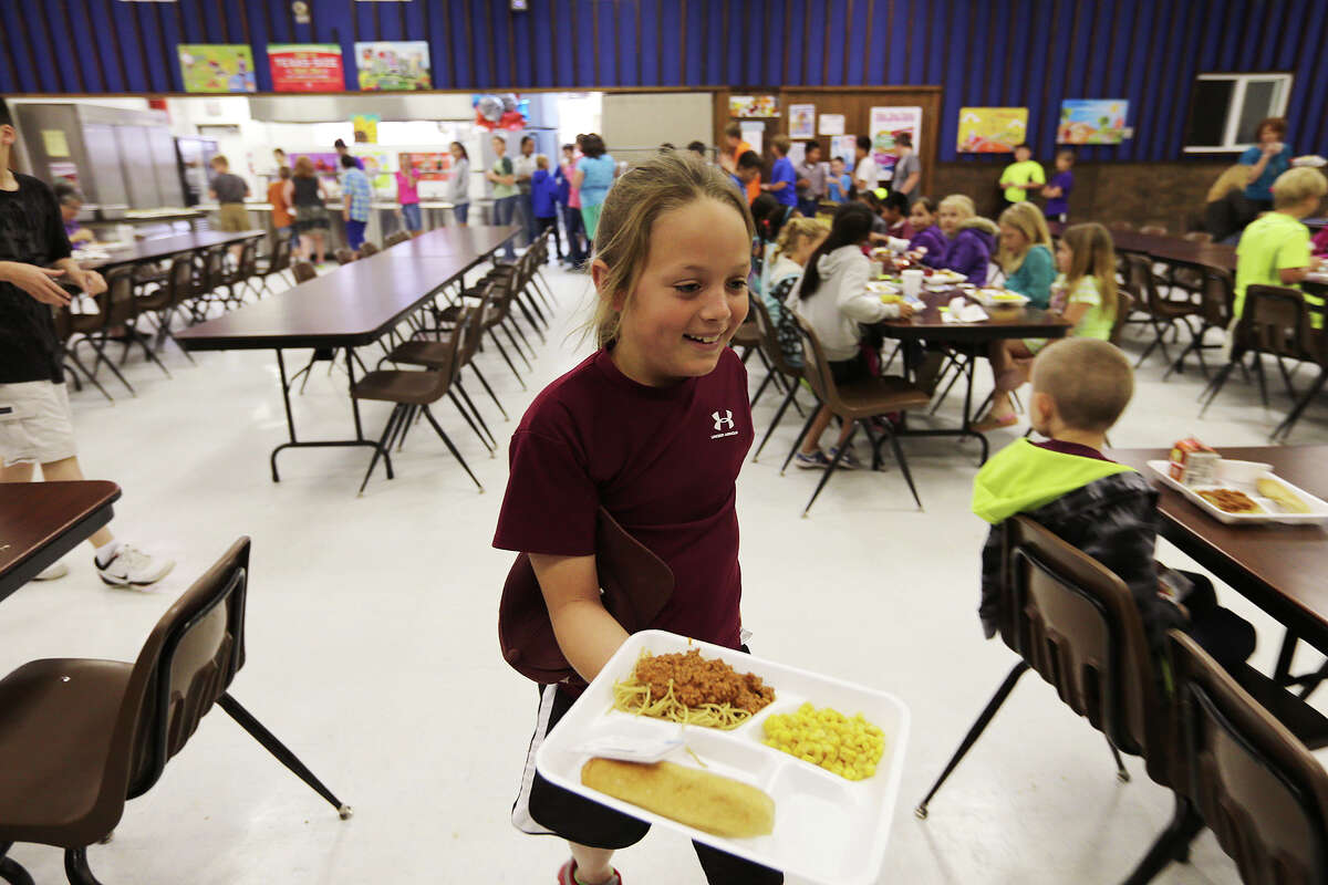 Third-grader Delaney Smith carries her lunch at the McMullen County Independent School District cafetorium, Tuesday, April 1, 2014. The district has a student population of 248 students. The population has increased by 100 students due to the boom from the Eagle Ford Shale play.