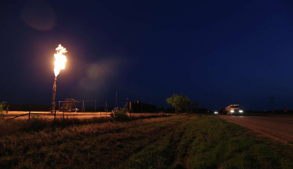 A well flares as traffic moves along Texas Highway 16 north of Tilden, Texas on Wednesday, April 2, 2014.