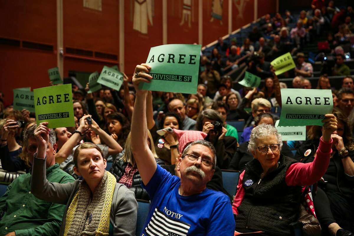 (l-r) Mimi Main and Greg Pennington (center) hold up signs as they agree with a comment made during a town hall meeting with Senator Dianne Feinstein at the Scottish Rite Masonic Center San Francisco, California, on Monday, April 17, 2017.
