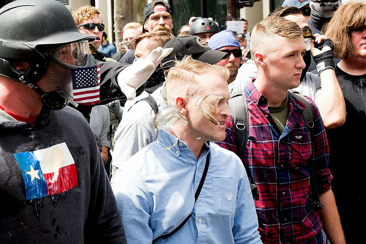 Broken glass flies by Nathan Damigo, founder of the white nationalist group Identity Evropa, as he faces off with counter-protesters during a conservative rally on Saturday, April 15, 2017, in Berkeley, Calf. Damigo studies social sciences at Cal State Stanislaus. Kyle Chapman, aka