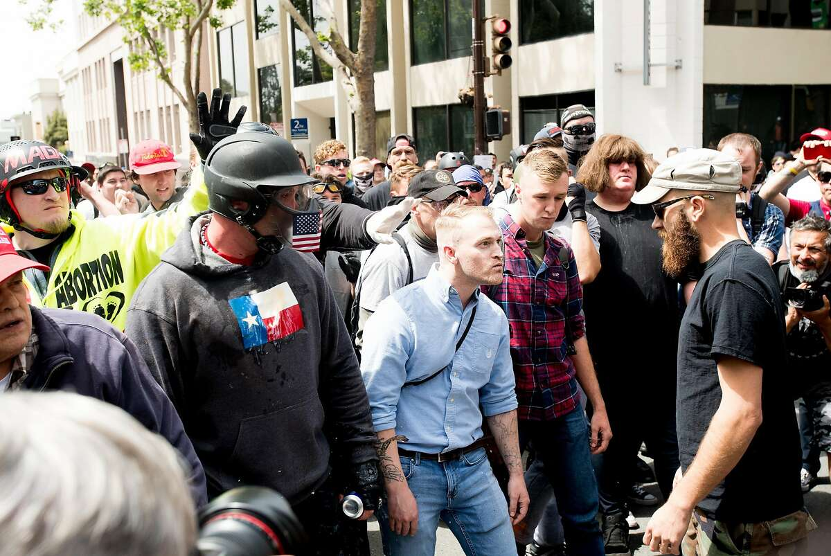 Identity Evropa founder Nathan Damigo, in a blue shirt at center, faces off with counter-protesters during a conservative rally on Saturday, April 15, 2017, in Berkeley, Calf. Damigo , who leads the white nationalist group, studies social sciences at Cal State Stanislaus. Kyle Chapman, aka