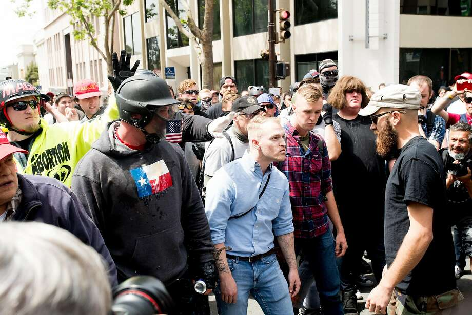 """Identity Evropa founder Nathan Damigo, in a blue shirt at center, faces off with counter-protesters during a conservative rally on Saturday, April 15, 2017, in Berkeley, Calf. Damigo , who leads the white nationalist group, studies social sciences at Cal State Stanislaus. Kyle Chapman, aka """"Based Stickman,"""" is pictured at left in helmet. Photo: Noah Berger, Special To The Chronicle"""