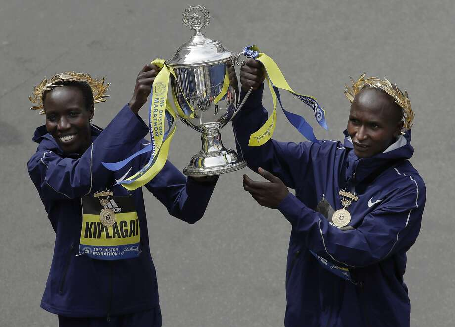 Edna Kiplagat (left) and Geoffrey Kirui, both of Kenya, hold a trophy together after their victories in the Boston Marathon. Photo: Charles Krupa, Associated Press