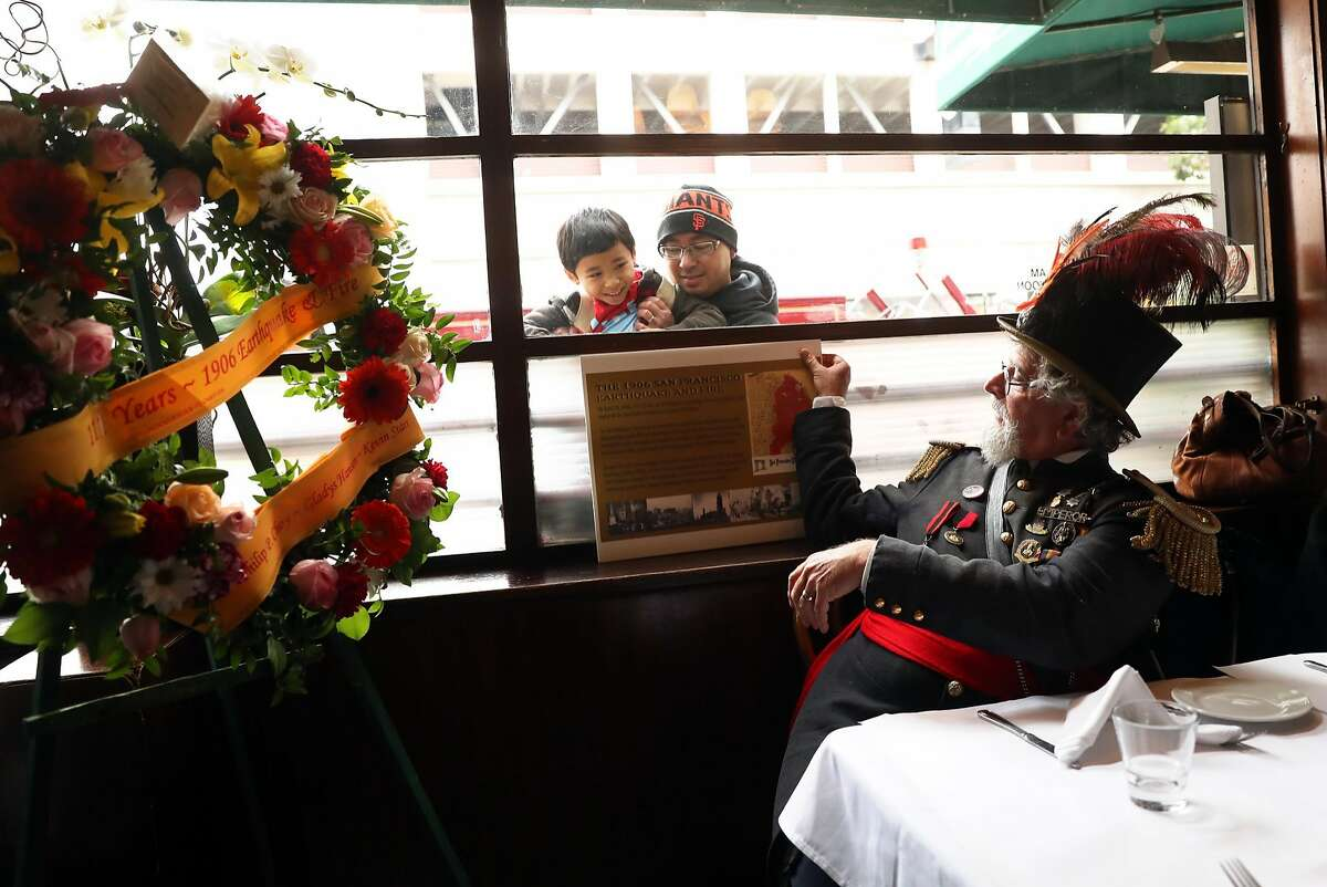 Joseph Amster aka Emperor Norton places a commemorative plaque design as two passersby peer in at a luncheon commemorating the 111th Anniversary of the Great San Francisco 1906 Earthquake and Fire in San Francisco, Calif., on Monday, April 17, 2017.