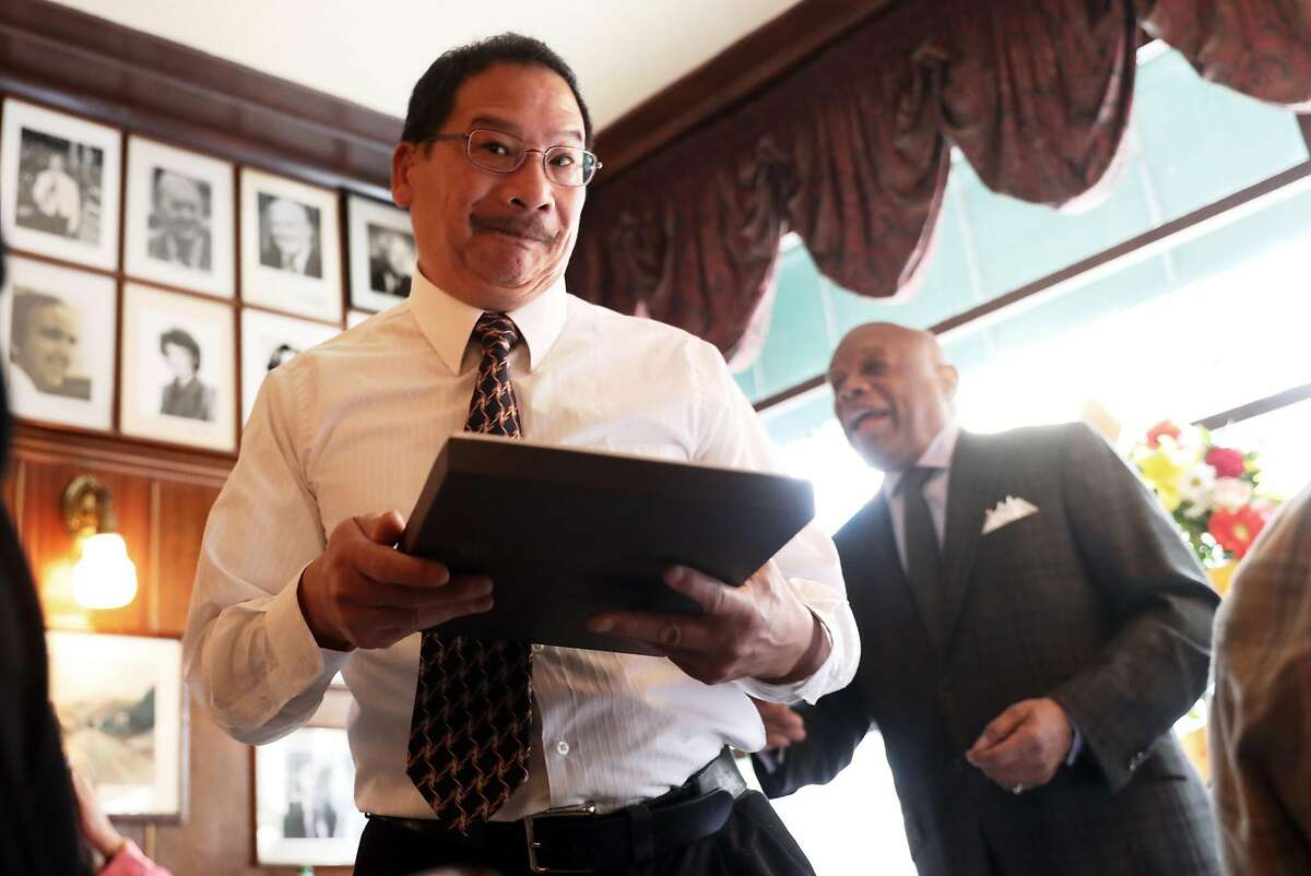 Brian Choy, emotionally accepts a plague honoring his late father, historian Philip Choy, from former S.F. Mayor Willie Brown (right).