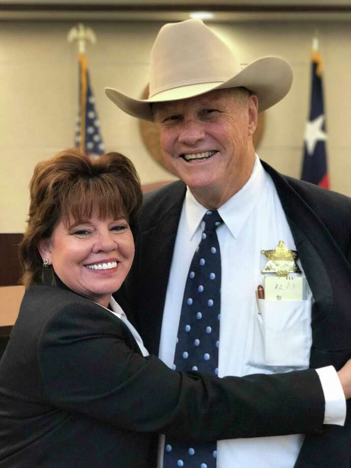 Sherry Cook pins a sheriff's badge on husband Maurice Cook, elected as Bastrop County's top law enforcement officer Nov. 8, 2016. Cook is executive director of the Texas Alcoholic Beverage Commission. MARY HUBER / BASTROP ADVERTISER Photo: Mary Huber, Bastrop Advertiser / 2016 Mary Huber / Bastrop Advertiser