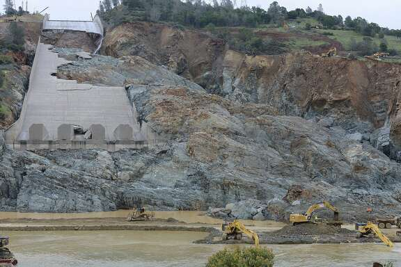 Crews work near the Oroville Dam spillway Thursday, April 6, 2017, in Oroville, Calif. Gov. Jerry Brown waived some permitting and review requirements Thursday for Oroville Dam as California rushes to repair a main spillway that partially washed away under heavy winter runoff. (Dan Reidel/The Chico Enterprise-Record via AP)