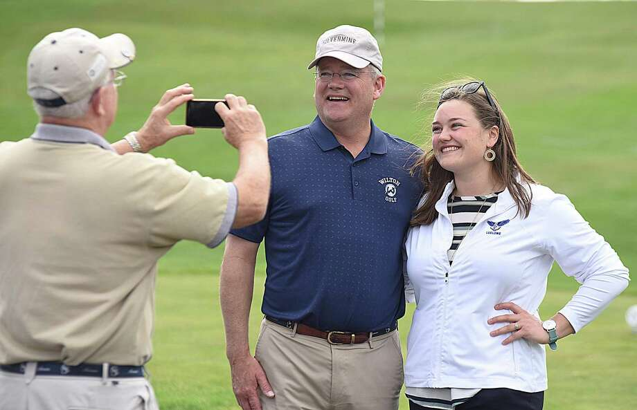 Stuart Waack, center, and his daughter Lindsay, right, have their picture taken together by a family friend before the start of Monday's FCIAC girls golf match between Wilton and Fairfield Ludlowe at the Silvermine Golf Club in Norwalk. Stuart Waack founded the girls program at Wilton while Lindsay is the first-year head coach at Ludlowe. Photo: John Nash / Hearst Connecticut Media / Norwalk Hour