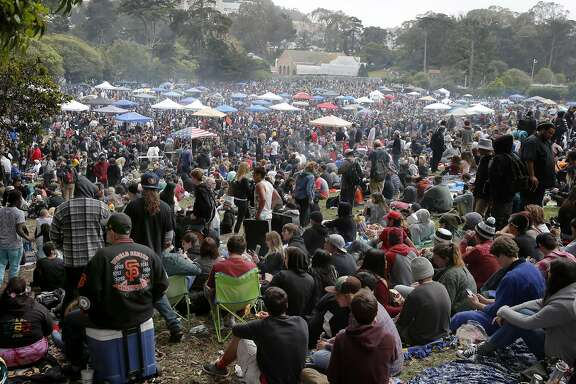 People gathered in the meadow on an overcast afternoon. The annual four twenty celebration of marijuana smoking was attended by thousands near Hippie Hill in Golden Gate Park.
