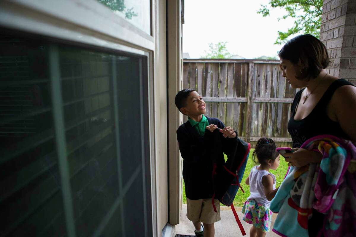 Rose Marie Escobar, 31, returns home with her children Walter Escobar, 7, and Carmen Marie Escobar, 2, from picking up Walter from a bus stop, Tuesday, April 11, 2017, in Pearland. Normally Rose's husband would be the one to pick up Walter while Rose prepared dinner, but not anymore since Jose was deported to El Salvador.