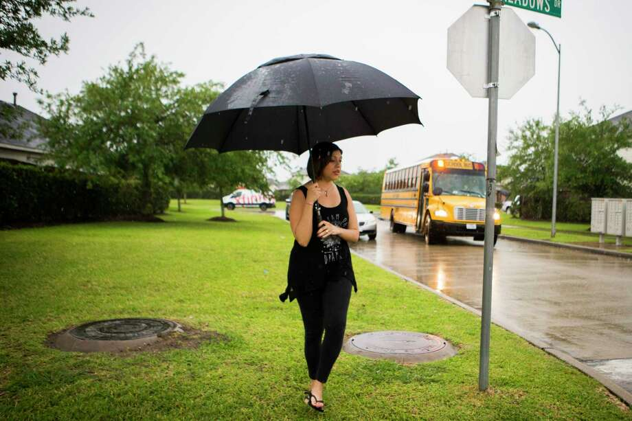 Rose Marie Escobar, 31, waits in the rain for the arrival of her son Walter Escobar, 7, from school, Tuesday, April 11, 2017, in Pearland. Her husband Jose Escobar used to be the parent that would pick up Walter, but that was before he was deported to El Salvador. Photo: Marie D. De Jesus, Houston Chronicle / © 2017 Houston Chronicle