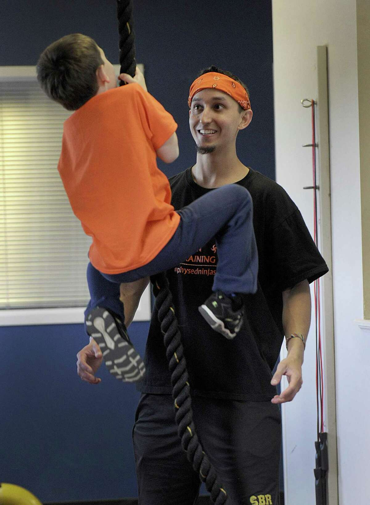 Jean Claude Chacon-Saucy guides Charlie Fergason, 6, of New Milford, through a Ninja-Warrior inspired set of challenges Monday, April 17, 2017. Chacon-Saucy will compete in the American Ninja Warrior TV show next month.
