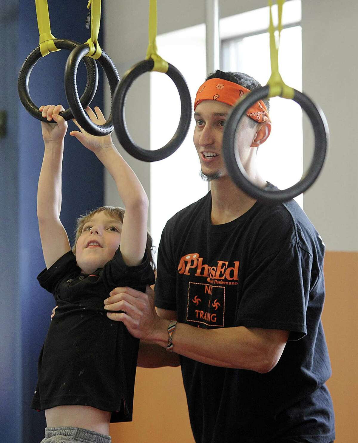 Jean Claude Chacon-Saucy guides Max Bonnell, 5, of Sherman, through a Ninja-Warrior inspired set of challenges Monday, April 17, 2017. Chacon-Saucy will compete in the American Ninja Warrior TV show next month.