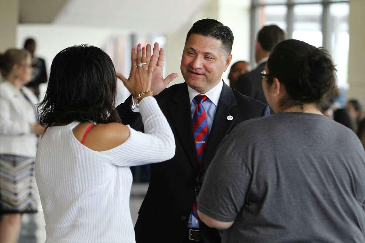 UH-Downtown's new president, Juan Sanchez Muñoz, greets students Antigua Ellis, left, and Tracy Garcia.
