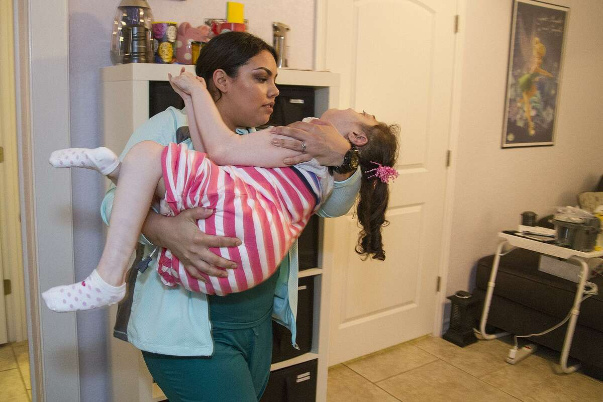 Nurse Damaris Patino carries Chloe, 10, to her bed. Under the state's Medically Dependent Children's Program, Chloe is provided nursing care at home.