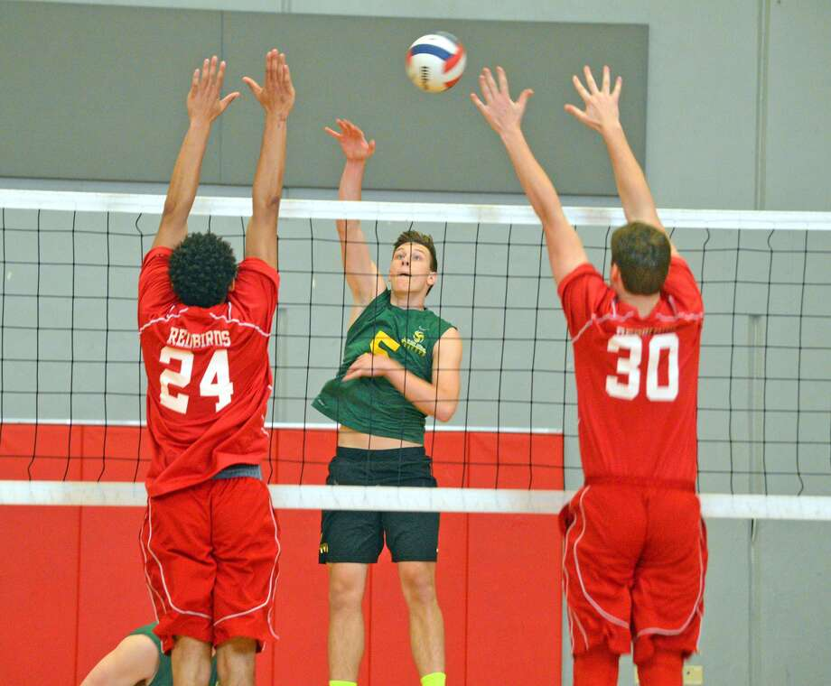 Metro-East Lutheran senior Braden Woolsey tries to hit between two Alton blockers in the first game of Monday's match.