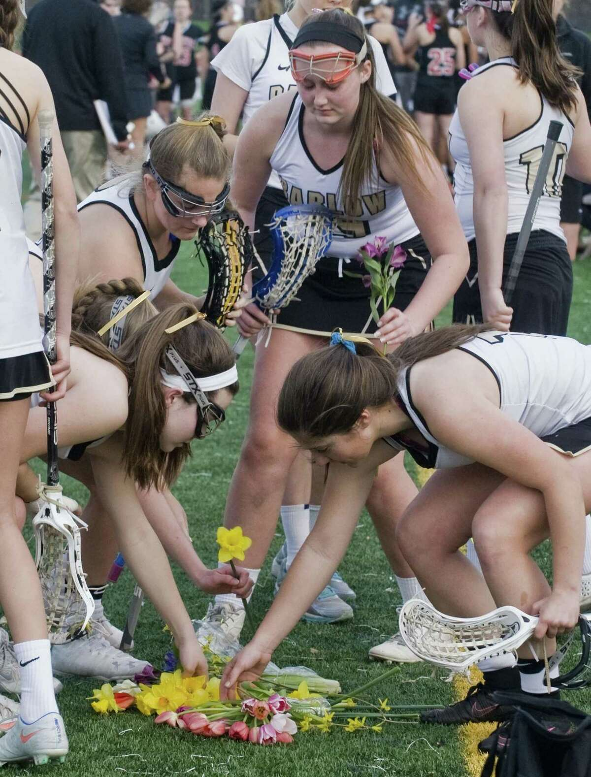 Joel Barlow High School girls lacrosse team members before their game on Monday select flowers for a moment of silence for their four classmates who were seriously injured in an automobile accident on Friday night.