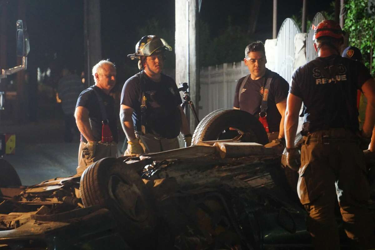 San Antonio Fire Department firefighters work to remove the body of a man in his 30s from a green Ford Mustang that landed upside down after a rollover Monday evening in the 7100 block of Somerset Road. The driver fled the scene but was found moments later near Somerset and Palo Alto roads, according to the San Antonio Police Department.