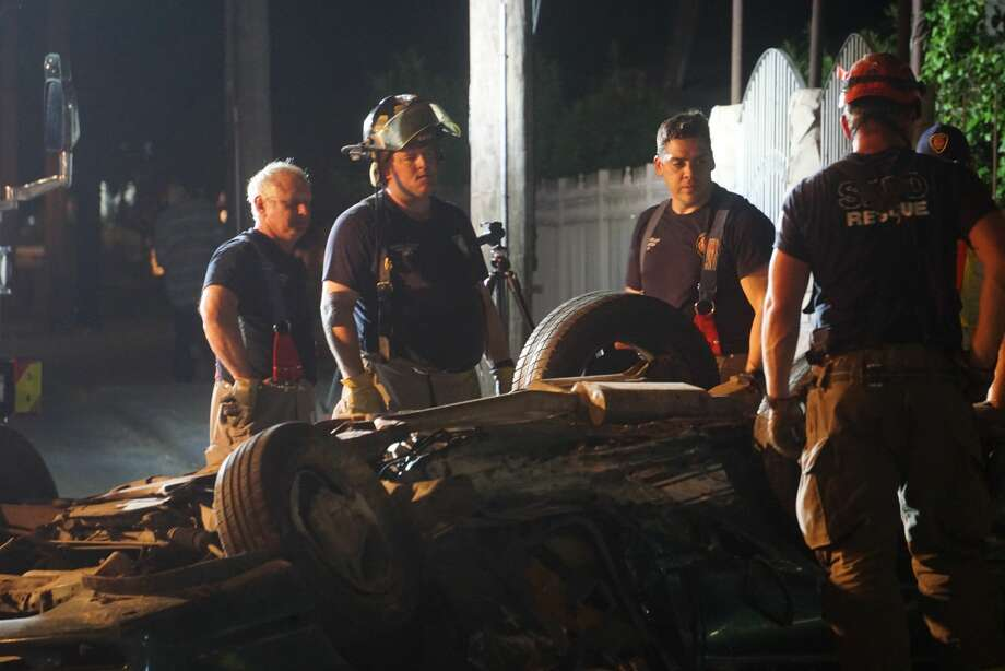San Antonio Fire Department firefighters work to remove the body of a man in his 30s from a green Ford Mustang that landed upside down after a rollover Monday evening in the 7100 block of Somerset Road. The driver fled the scene but was found moments later near Somerset and Palo Alto roads, according to the San Antonio Police Department. Photo: Jacob Beltran