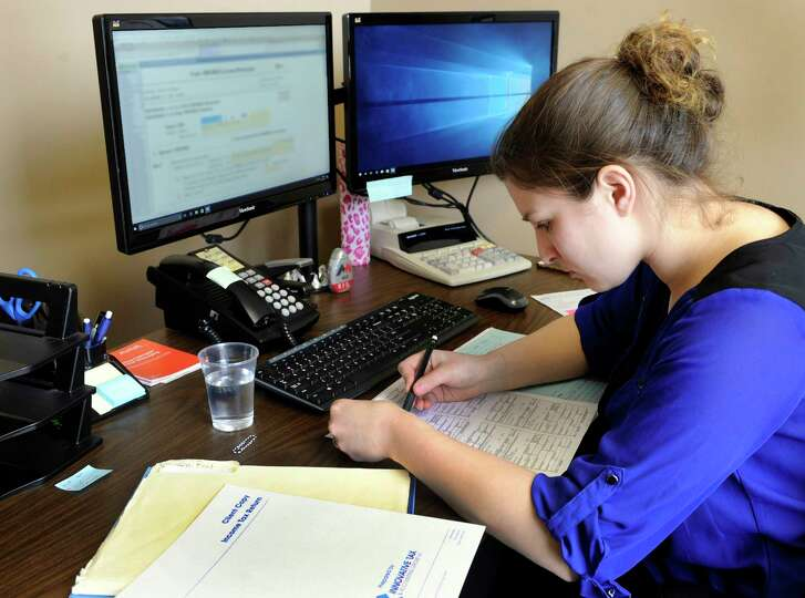 Nicole Meyers, 23, reviews tax returns Monday at Innovations Tax and Accounting Group in Brookfield, Conn.