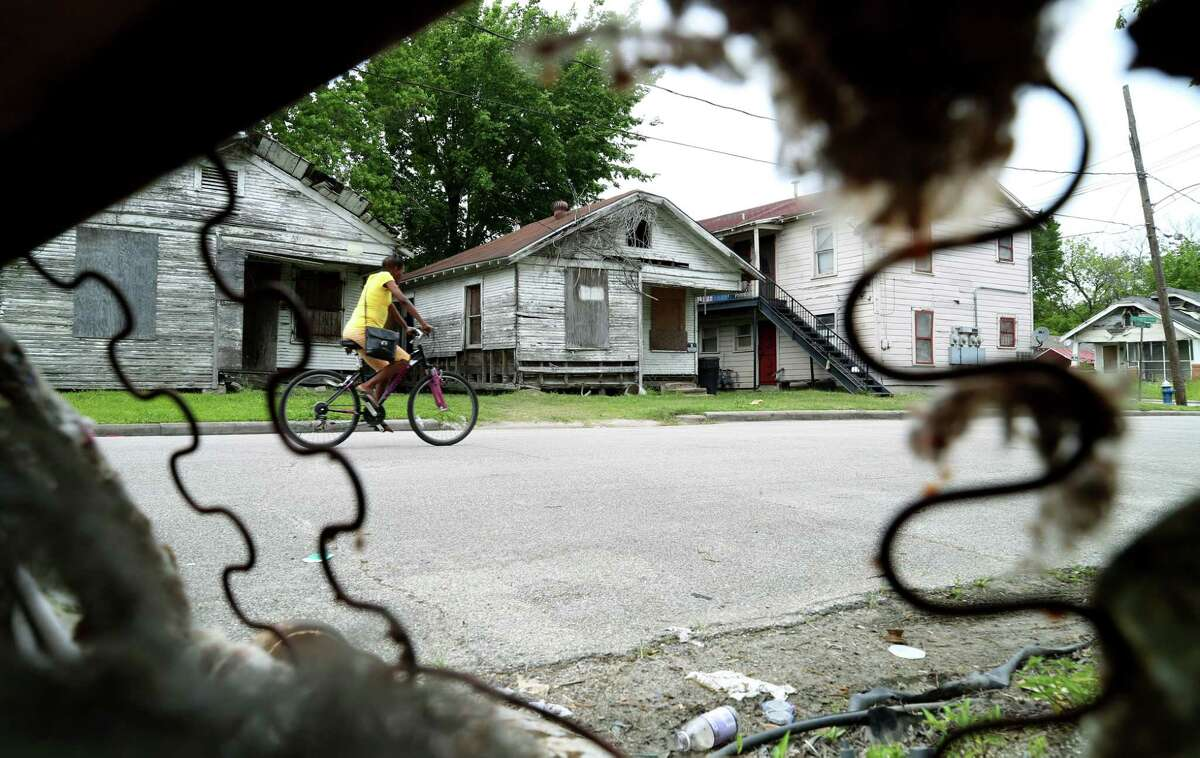Dilapidated houses are seen through the remnants of a couch on Canfield Street in Houston's Third Ward.
