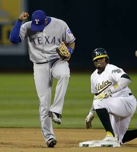 Texas Rangers Elvis Andrus, left, celebrates after making the out on Oakland Athletics' Rajai Davis in the first inning of a baseball game, Monday, April 17, 2017, in Oakland, Calif. Davis was tagged out on an attempted steal of second base. (AP Photo/Ben Margot)