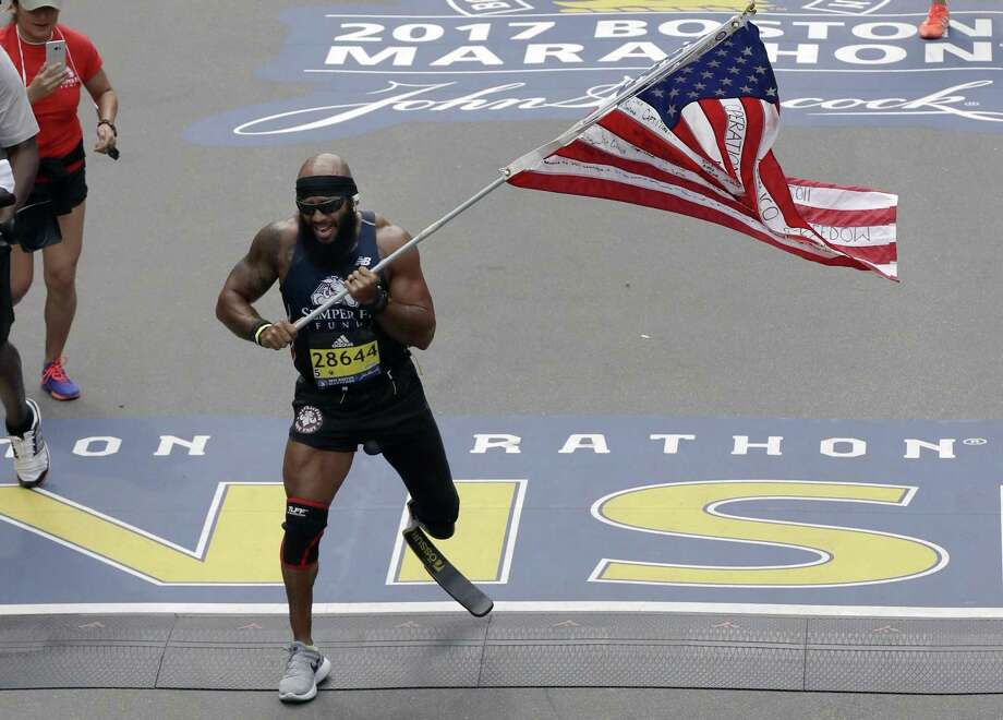 Jose Sanchez, of San Antonio, carries the United States flag across the finish line in the 121st Boston Marathon on Monday in Boston. Photo: Charles Krupa /AP / Copyright 2017 The Associated Press. All rights reserved.