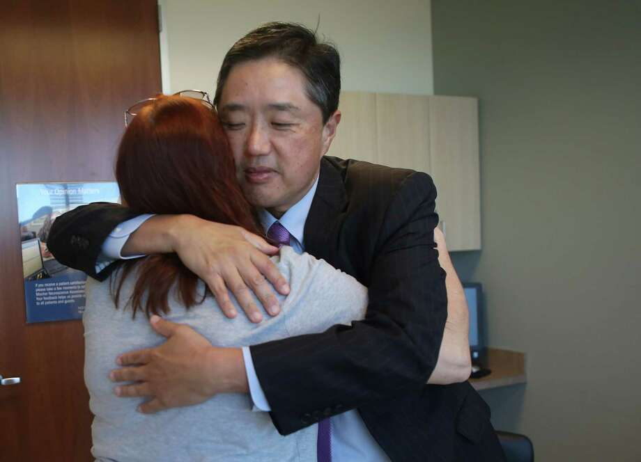 Dr. Dong Kim, the head of neurosurgery at Memorial Hermann Hospital, hugs Gina Sharp, of Baytown, at the end of a consultation regarding Sharp's brain aneurysm, Tuesday, Dec. 6, 2016, in Houston. Dr. Kim's research has discovered a gene mutation linked to brain aneurysms. ( Mark Mulligan / Houston Chronicle ) Photo: Mark Mulligan, Staff / © 2016 Houston Chronicle